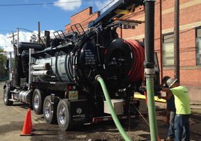 Hydro excavator with operators from public utilities working on municipal sewer and water system maintenance
